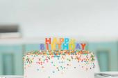 finom születésnapi torta színes gyertyákkal és boldog születésnapi felirattal