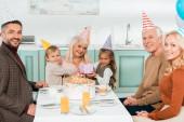 Fotografie veselé děti sedí na kolech babičky, zatímco sedí v blízkosti narozeninového dortu s rodinou
