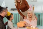Fotografie abgeschnittene Ansicht der Frau, die Schultern der glücklichen Oma berührt, die Geschenkbox vom Enkel nimmt