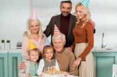 šťastná rodina ve party čepice při pohledu na narozeninový dort s hořícími svíčkami