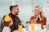 boldog férj és feleség nézik egymást, miközben ül a konyhaasztalnál a fiával közel születésnapi torta