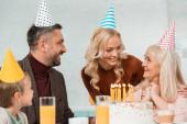 veselá rodina při pohledu na šťastný senior žena sedí v blízkosti narozeninového dortu