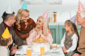 smiling woman touching shoulders of happy senior woman while all family sitting near birthday cake
