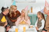 usmívající se žena dotýká ramena šťastné starší ženy, zatímco všechny rodiny sedí v blízkosti narozeninového dortu