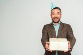 šťastný muž ve straně čepice držení dárkové krabice při pohledu na kameru izolované na šedé