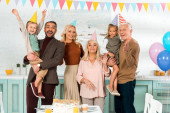 Photo happy family standing near kitchen table with birthday cake and looking at camera