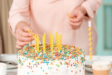 Cropped view of senior woman putting candles in delicious birthday cake stock vector