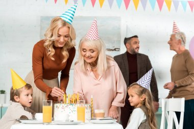 Happy women putting candles in birthday cake near family in party caps stock vector