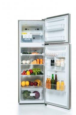 open fridge and freezer with fresh food on shelves isolated on white