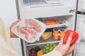 Fotografie abgeschnittene Ansicht eines Mannes mit gefrorenem Fleisch und frischem Paprika in der Nähe eines offenen Kühlschranks voller Lebensmittel
