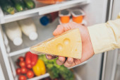Fotografie cropped view of man holding cheese near open fridge full of food