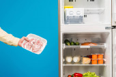 abgeschnittene Ansicht eines Mannes, der gefrorenes Fleisch in der Nähe von offenem Kühlschrank und Tiefkühltruhe mit frischen Lebensmitteln in blau isolierten Regalen hält