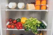 nyitott hűtőszekrény tele friss ételekkel a polcokon