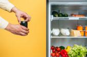 kivágott kilátás férfi nyitó doboz szódával közel nyitott hűtőszekrény friss élelmiszer polcokon izolált sárga