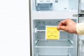 oříznutý pohled na muže držícího smutný úsměv poblíž prázdné otevřené ledničky izolované na bílém