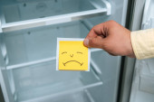 Photo cropped view of man holding sad smiley near empty open fridge