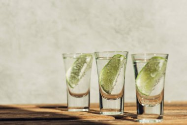Selective focus of fresh tequila with lime on wooden surface in sunlight stock vector
