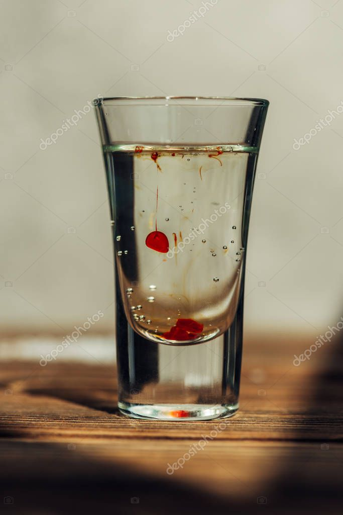 Close up view of shot with transparent and red liquid on wooden surface in sunlight stock vector