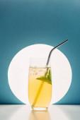 frische Limonade mit Minze und Stroh auf blauem Hintergrund mit Gegenlicht