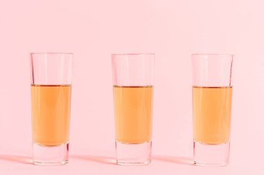 Three shots with alcohol in row on pink background stock vector