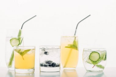 Refreshing drinks with blueberries, celery, straws, mint, cucumber and ice isolated on white stock vector