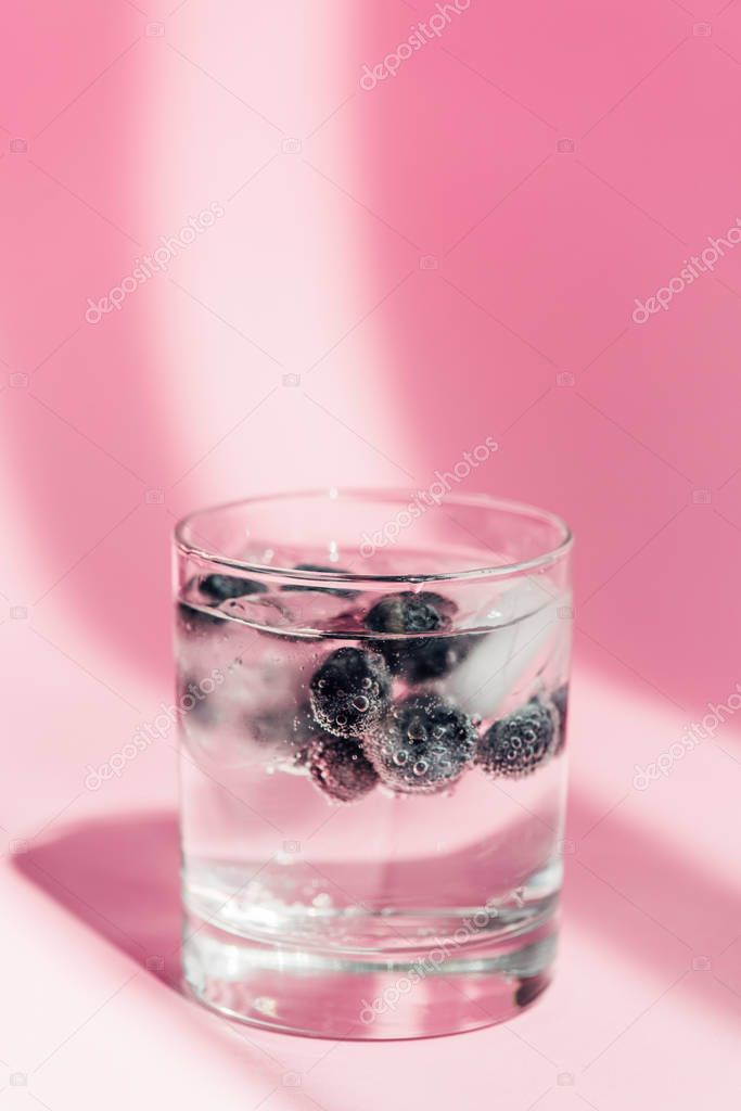 Fresh lemonade with ice and blueberries in sunlight on pink background stock vector