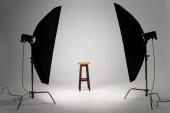 Dřevěná stolička se studiovým světlem na šedém pozadí