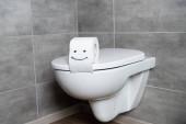Mosoly felirat WC-papír fehér WC-ülőke fürdőszoba szürke csempe