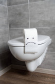 Sad emoticon on toilet paper on ceramic toilet bowl in bathroom