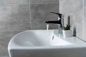 Photo Water flow from sink to ceramic washbasin with plant in modern restroom