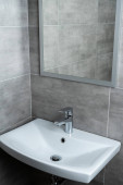 Keramické umyvadlo se zrcadlem v moderní umývárně s šedou dlažbou