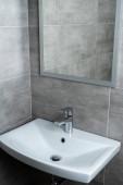 Photo Ceramic washbasin with mirror in modern washroom with grey tile