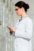Seitenansicht der schönen Apothekerin mit digitalem Tablet in der Drogerie