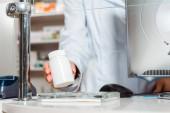Vágott nézet a női gyógyszerész üzembe üveg tabletták a pultra