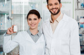 Smiling pharmacists with pills looking at camera in drugstore
