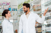 Side view of handsome pharmacist pointing at showcase to colleague in drugstore