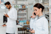 Selective focus of pharmacist with clipboard talking on smartphone with colleague at background