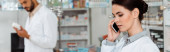 Panoramic shot of pharmacist talking on smartphone with colleague at background