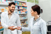Smiling pharmacist giving to colleague jar with pills in pharmacy