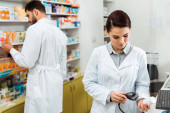 Pharmacist scanning jar of pills with barcode scanner with colleague at background