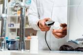 Fotografie Ausschnittansicht des Apothekers, der Pillen mit Barcode-Scanner in Drogerie scannt