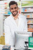 Fotografie Schöner lächelnder Apotheker mit Terminal an der Drogerietheke