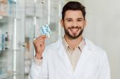 Schöner Apotheker lächelt in die Kamera, während er Blase mit Pillen hält