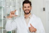 Fotografie Apotheker mit Pillen-Glas lächelt in die Kamera und zeigt Daumen hoch