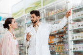 Handsome pharmacist pointing at showcase to customer