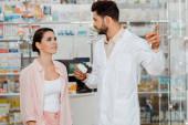 Fotografie Apotheker hält Tablettendose in der Hand und zeigt auf Schaufenster zum Kunden