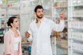 Fotografie Apotheker mit Pillen-Glas zeigt Kunden auf Apothekenvitrine