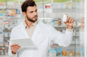 Fotografie gutaussehender Drogist mit digitalem Tablet und Blick auf Pillen