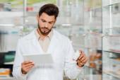 Fotografie gutaussehender Drogist mit digitalem Tablet in der Apotheke