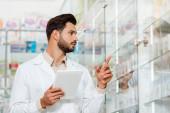Schöne Apothekerin mit digitalem Tablet zeigt auf Vitrine in Apotheke